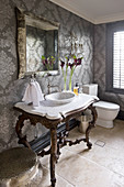 Antique washstand with marble top in bathroom with ornately patterned wallpaper