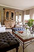 Klassisches Wohnzimmer mit Polsterhockern und antikem Schrank