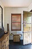 Offene, rustikale Haustür aus Holz mit Metallbeschlägen im Eingang