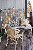 Wicker chair, table with elephant-head legs and ornate metal bench