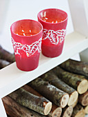 Two red tea light glasses with a Christmas leaf motif
