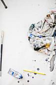 Painter's utensils and dirty towel on floor