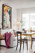 Cosy dining area with sofa and painting in tiled kitchen