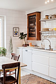 Old glass-fronted cabinet in white kitchen with white-tiled walls