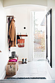 Coat rack and full-length mirror in white hallway with open front door