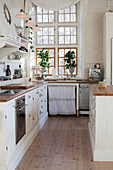 White kitchen counters with wooden worksurfaces and houseplants in front of lattice window