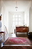 Rug and antique cabinet on landing in period building
