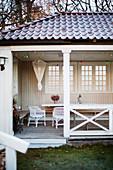 Table, rattan armchair and fairy lights in summerhouse with lattice windows