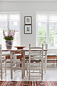 White country-house chairs around wooden table with battered paint