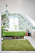 White-and-green bedroom with sloping ceiling and jungle-patterned wallpaper