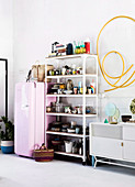 Open shelf with crockery next to pink fridge, yellow hose as wall decoration