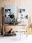 White chair and desk, mood board on wooden wall above