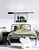 Metal bed with green bedding, above picture with horse motif and paddle