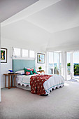 Double bed with a high mint green headboard in a light-flooded beach house