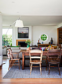 Dining table with rustic wooden chairs, in the background a seating area with a modern fireplace