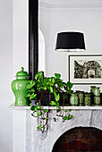Green vases and houseplant on mantelpiece