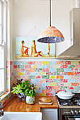 Fitted kitchen with wooden worktop and colorful wall tiles