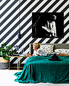 Large-format photography on a black and white striped wall, blonde woman lying on bed with green day cover