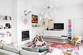 Weißes Wohnzimmer mit bunten Accessoires, lesende Mädchen auf dem Teppich