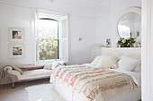 Double bed with bedspread and chaise longue in front of window in white bedroom