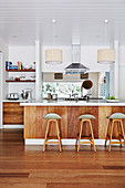 Bar stool on kitchen island with wooden front, white wooden ceiling in open kitchen