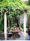 Rustic wooden table with chairs under pergola with wisteria