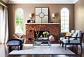 Upholstered chairs, coffee table and upholstered bench in front of a fireplace