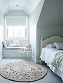 White bed under sloping ceiling, round carpet and built-in bench under window in girl's room