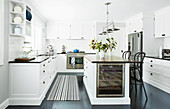 Kitchen island with wine cooler and bar stool in white kitchen dark floor