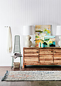 Sideboard with table lamp and works of art on white wall