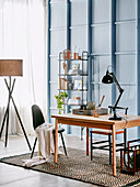 Wooden table with articulated lamp, open shelf and floor lamp in the study