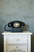 Old telephone on cabinet against mottled grey wall