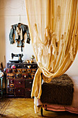 Artistically draped curtains in front of designer jacket on wall above vintage sewing machine on chest of drawers