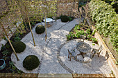 View down into courtyard with table and chairs on gravel terrace