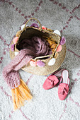Knitted scarf in basket with pompoms next to ladies' shoes