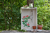 Shelf unit made from old wooden crate and decorated with wild-rose motif