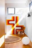 Designerstuhl und grafisches Bild vor einem Oberlichtfenster