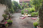 Vintage table, chairs and potted plants on terrace