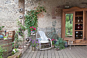 Large storage jars in wooden cupboard and rocking chair on roofed terrace