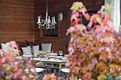 Gedeckter Tisch, darüber Kronleuchter in herbstlichem Ambiente