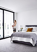 Woman and baby at balcony window in light gray bedroom