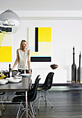 Woman sets the table in the modern dining room with yellow pictures