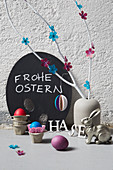 Vase of branches decorated with paper flowers, Easter bunny and Easter eggs in egg box cells