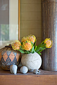Protea flowers in rustic spherical vase