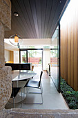 View into open-plan interior with sliding door opening onto light well