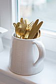 Gold cutlery in jug with checked embossed pattern