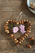 Heart of threaded acorns and pink chrysanthemums