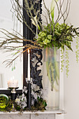 Vase of green flowers and branches on mantelpiece