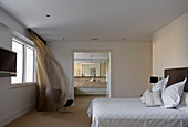 Double bed in minimalist bedroom with view into ensuite bathroom
