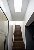 Treppenhaus mit dunklen Holztreppen und Oberlicht